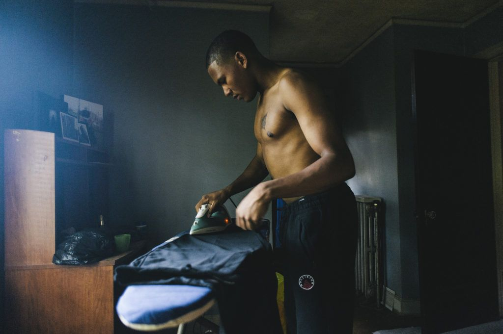 Logan Sloan, 20, irons his graduation gown at home as he prepares for his graduation ceremony later in the day, at which he will receive his high school diploma from the Covenant House Academy in Detroit, Michigan. June 14th, 2016.